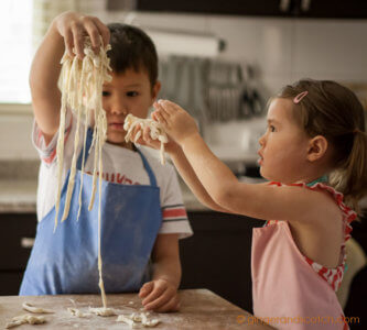 Kids fluffing strands of making homemade Chinese