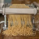 Cutting the noodle dough with the spaghettini-sized cutter to make homemade Chinese egg noodles from scratch